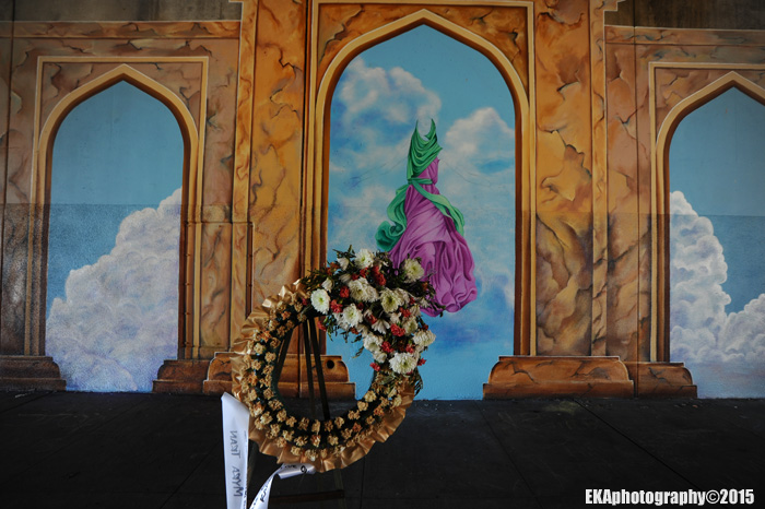 A wreath for slain muralist Antonio Ramos hangs in front of the mural site