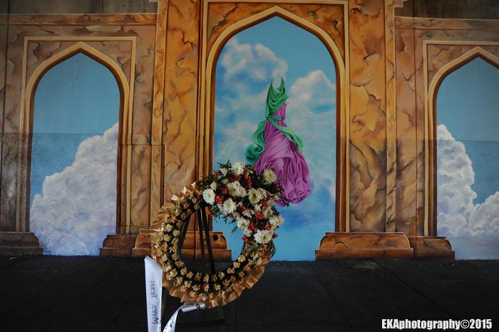 A wreath for slain muralist Antonio Ramos hangs in front of the mural site